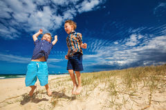 Young happy boys having fun on tropical beach, jumping into the Stock Images