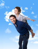 Young happy Brazilian father carrying on his back  little son as airplane flying having fun together on a blue sky Royalty Free Stock Images