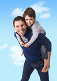 Young happy Brazilian father carrying on his back little son smiling and having fun together Stock Image