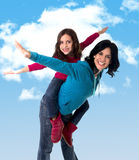 Young happy Brazilian mother carrying on her back  little daughter as airplane flying Stock Image