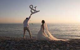 Young happy bridal couple having fun at edge of water Royalty Free Stock Photo