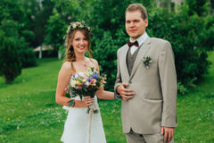 Young happy bride and groom on the background of greenery Royalty Free Stock Photography