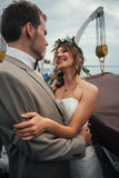 Young happy bride and groom in a boat on the background of buildings Stock Photography