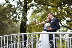 Young happy bride and groom standing on a bridge while bride poi Stock Photos