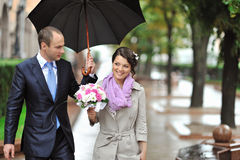 Young happy bride and groom walking by the rain Stock Image