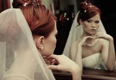 Young happy bride. Young bride looks at herself in the mirror royalty free stock photography