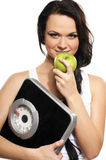 A young and happy brunette is eating a green apple Stock Images