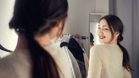 Young and happy brunette female in clothes store smiling and choosing new things royalty free stock photography