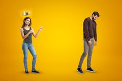 Young happy brunette girl in casual clothes with a golden crown above and a sad man in casual clothes on yellow royalty free stock image