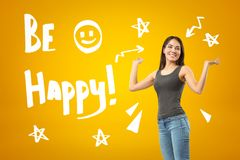 Young Happy Brunette Girl Wearing Casual Jeans And T-shirt With BE HAPPY Sign And Cartoon Stars And Smiley On Yellow Royalty Free Stock Images