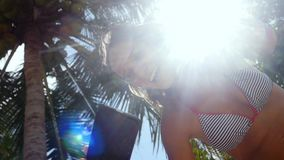 Young happy brunette laughing woman standing near palm tree and making selfie on mobile phone on a blue sky and the sun. Young happy brunette woman standing near stock video footage