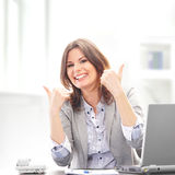 A young and happy brunette woman holding thumbs up Royalty Free Stock Photo