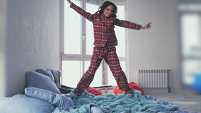 Young happy brunette woman jumping on bed wearing pajamas and smiling at camera Royalty Free Stock Image