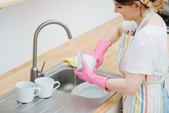Young happy woman in a kitchen is washing cups and dishes stock photo