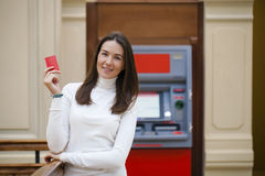Young happy brunette woman withdrawing money from credit card at Royalty Free Stock Photo