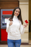 Young happy brunette woman withdrawing money from credit card at Stock Image
