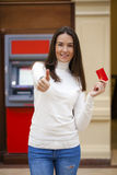 Young happy brunette woman withdrawing money from credit card at Stock Images