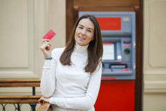 Young happy brunette woman withdrawing money from credit card at Stock Photo