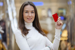 Young happy brunette woman withdrawing money from credit card at Royalty Free Stock Photos