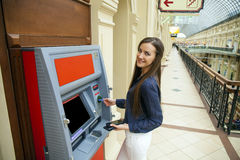 Young happy brunette woman withdrawing money from credit card at Royalty Free Stock Image