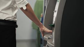 Young happy brunette woman withdrawing money from credit card at ATM in shopping mall,