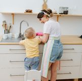 Young happy woman in a kitchen is washing cups and dishes. Her little son helps royalty free stock image