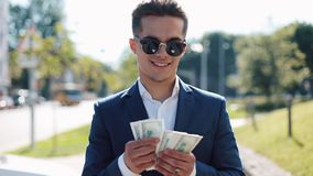 Young happy businesman in sunglasses and a suit counting money and walking in the street. He selebrating his successful