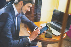 Young happy businesman working at cafe, using mobile phone. And laptop. Successful. Onlin payment by plastic card through the Internet Banking Royalty Free Stock Image