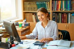 Young happy business lady in white shirt sitting at table with computer and papers working environment.  royalty free stock images