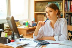 Young happy business lady in white shirt sitting at table with computer and papers working environment.  royalty free stock photos