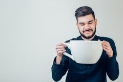 Business man holding a funny huge and oversized cup of black coffee in caffeine. Young happy business man holding a funny huge and oversized cup of black coffee Stock Photos