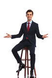 Young happy business man sitting on chair and welcoming you Stock Photos
