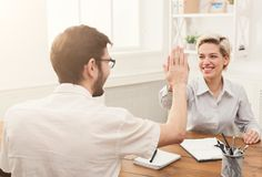 Young happy business partners in office. Winner business partners happy, successful, in white modern office, sitting at workplace. Colleagues giving high five Royalty Free Stock Photos