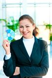 Young happy business woman with a CD in hand. On blurred background office Stock Images