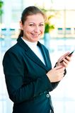 Young happy business woman with a mobile phone in hand. On the phone on office background Royalty Free Stock Photography