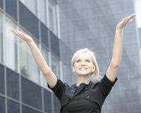 A young and happy business woman showing success. A young and happy business woman is rising her hands up as a sign of success. Image taken outdoors, on a modern Royalty Free Stock Photos