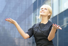 A young and happy business woman showing success. A young and happy business woman is rising her hands up as a sign of success. Image taken outdoors, on a modern Stock Photo