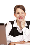 Young happy business woman sits on desk in office Royalty Free Stock Image
