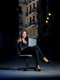 Young Happy Business woman sitting on Office Chair on Street with Laptop Stock Image