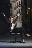 Young Happy Business woman sitting on Office Chair on Street with Laptop Royalty Free Stock Photography