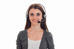 Young happy business woman in uniform with headphones and microphone looking at the camera and smiling isolated on white Royalty Free Stock Image
