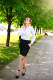 Young and happy business woman walking in city green park Stock Photos