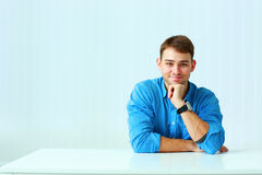 Young happy businessman in blue shirt sitting at the table Royalty Free Stock Images