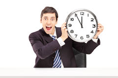 Young happy businessman holding a clock Royalty Free Stock Photography