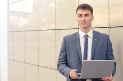Young and happy businessman with laptop. Smiling businessman with his laptop next to the office building Stock Images