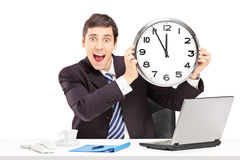 Young happy businessman in an office and holding a clock Royalty Free Stock Photos