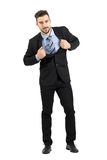 Young happy businessman pulling and stretching his suit jacket smiling at camera Stock Photos