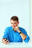 Young happy businessman sitting at the table and holding smartphone Stock Images
