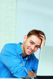 Young happy businessman sitting at the table with laptop Stock Photo
