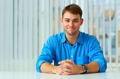 Young happy businessman sitting at the table Royalty Free Stock Image